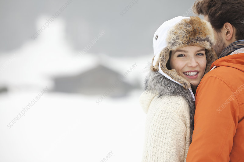 Smiling woman hugging man in snowy field