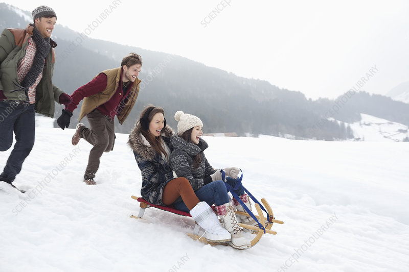 Enthusiastic friends sledding