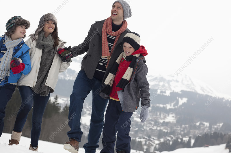 Happy family walking in snowy field