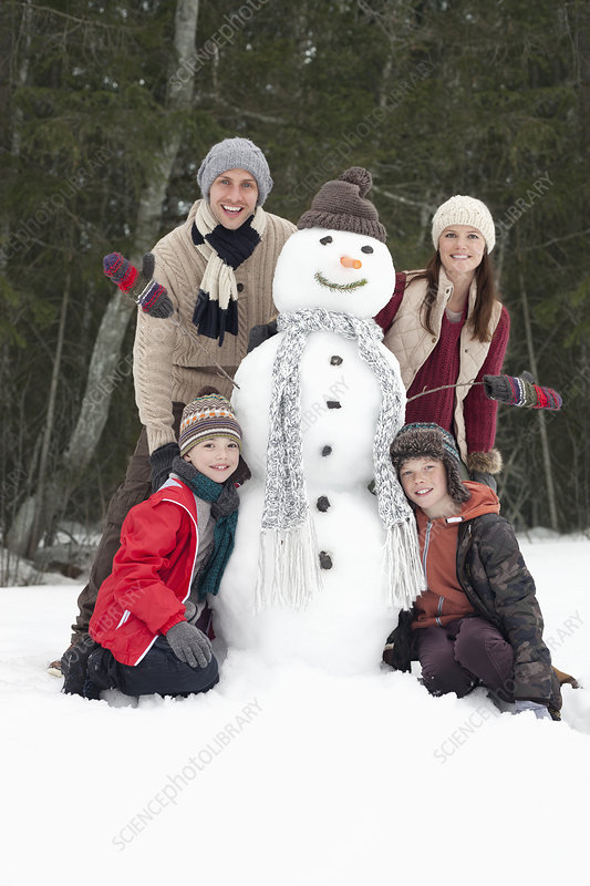 Portrait of happy family with snowman