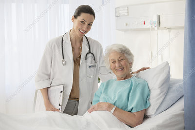 Portrait of doctor and aging patient room