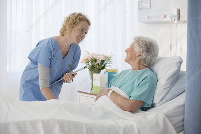 Nurse and aging patient talking room