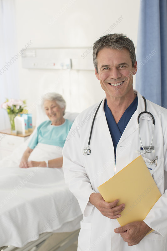 Smiling doctor with patient in background