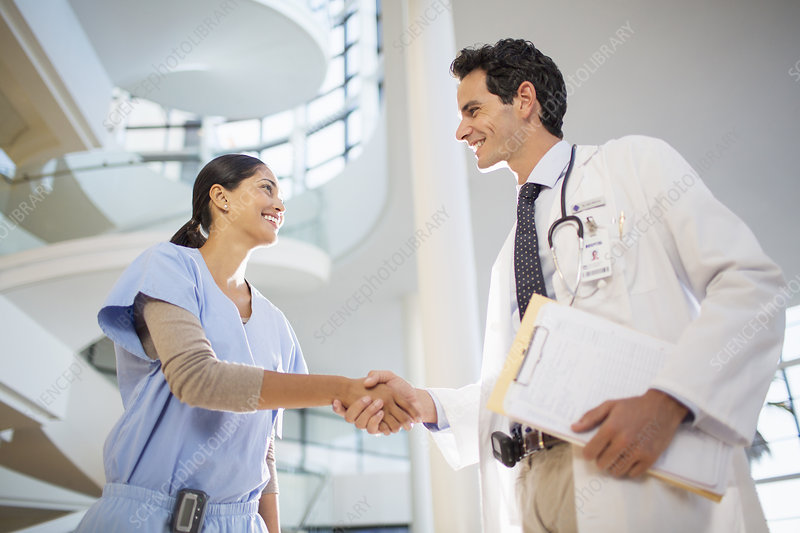 Doctor and nurse handshaking in hospital