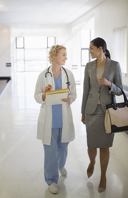 Doctor and businesswoman walking