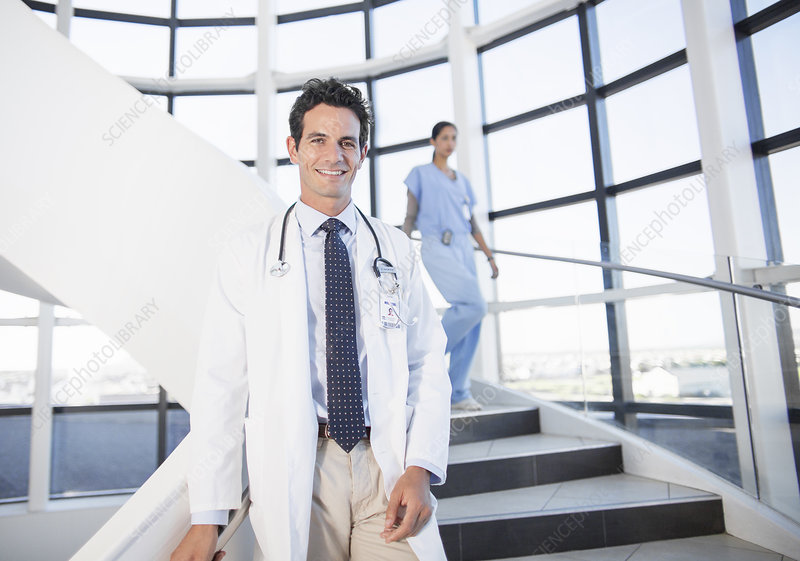 Smiling doctor on staircase in hospital
