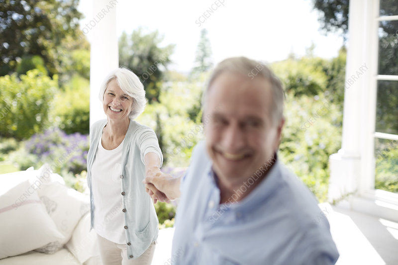 Senior couple holding hands on patio