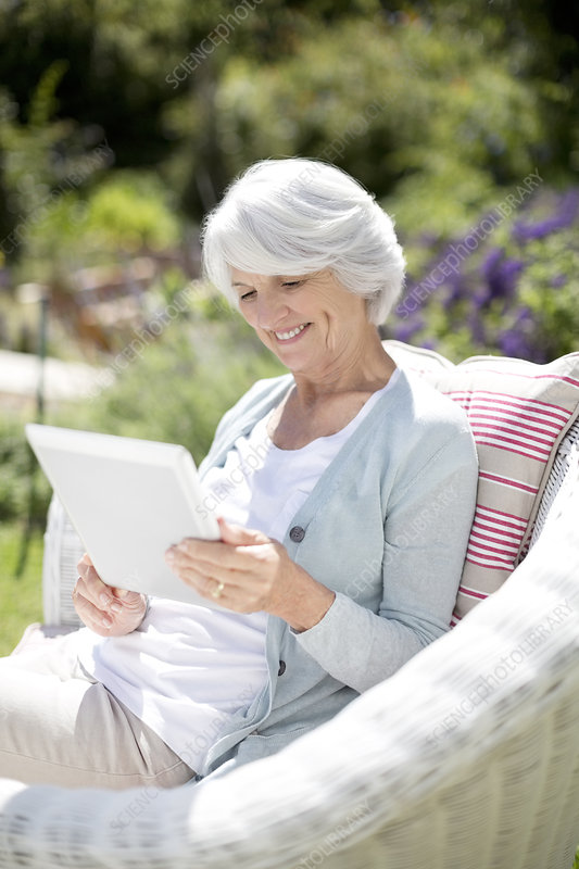Senior woman using tablet in armchair