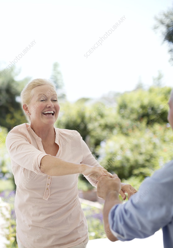 Senior couple dancing on patio