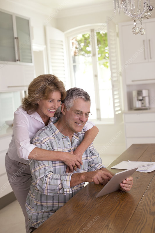 Senior couple using tablet in kitchen