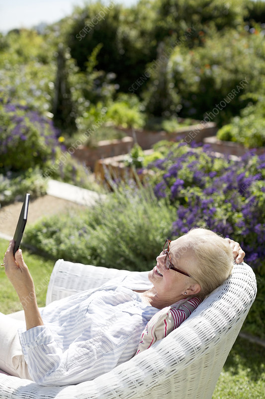 Senior woman using tablet in garden