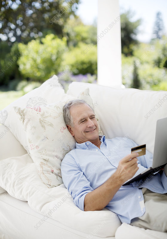 Senior man shopping online on patio sofa
