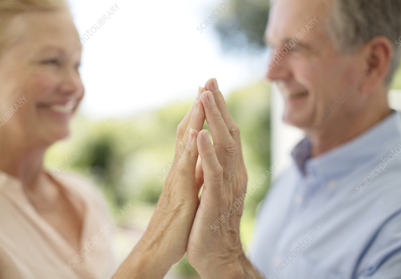 Senior couple touching hands on patio