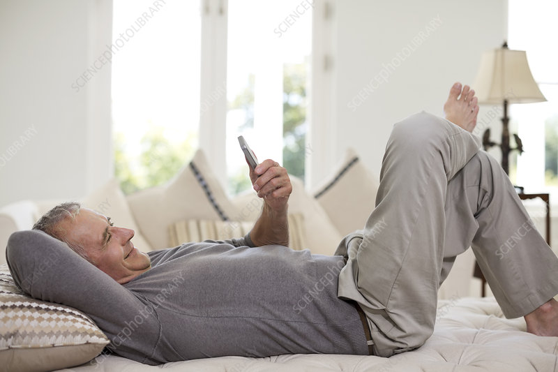 Senior man using cell phone on bed