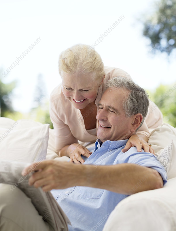 Senior couple reading newspaper sofa