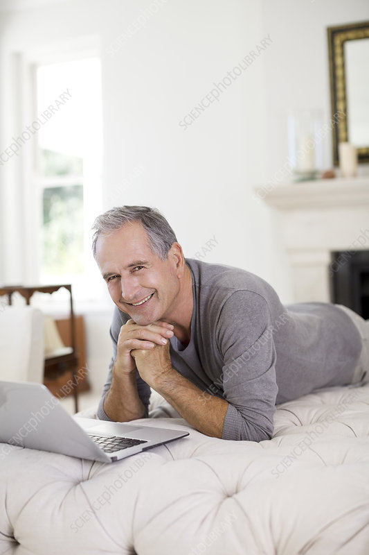 Senior man using laptop in living room