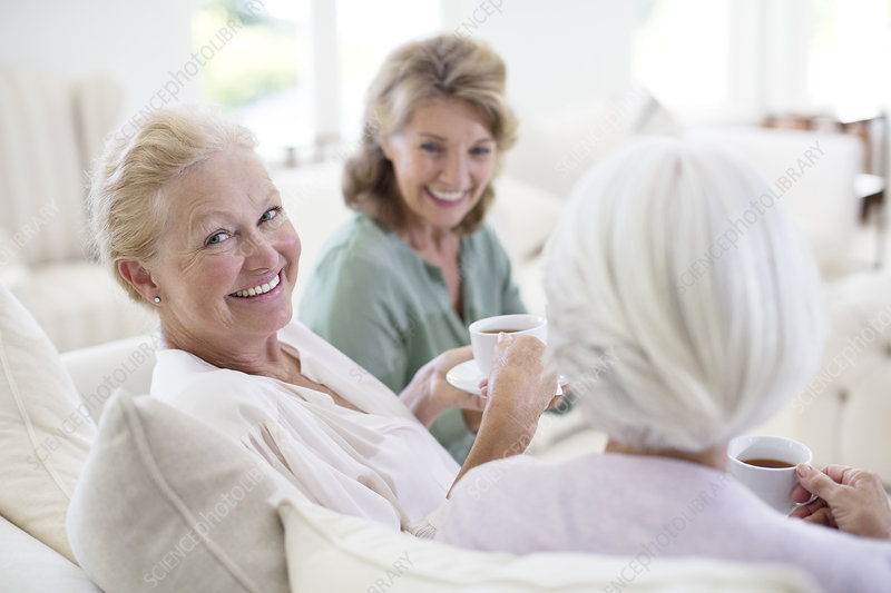 Senior women drinking coffee on sofa