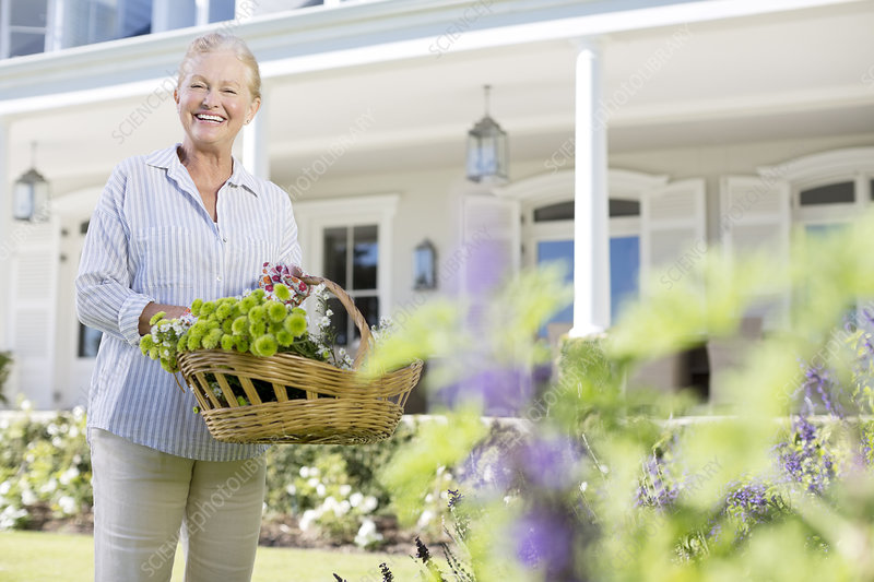 Senior woman picking flowers in garden