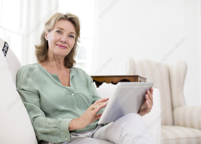 Senior woman using tablet on sofa