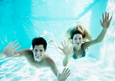 Smiling couple underwater in pool