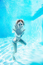 Smiling woman underwater in swimming pool