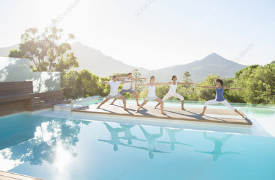 People practicing yoga at poolside