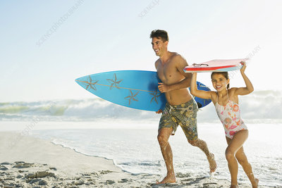 Father and daughter carrying surfboard