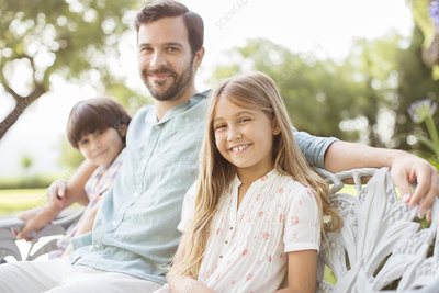 Father and children smiling on bench