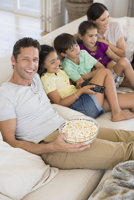 Family watching TV on sofa in living room