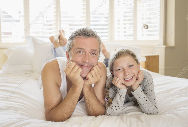 Father and daughter laying on bed