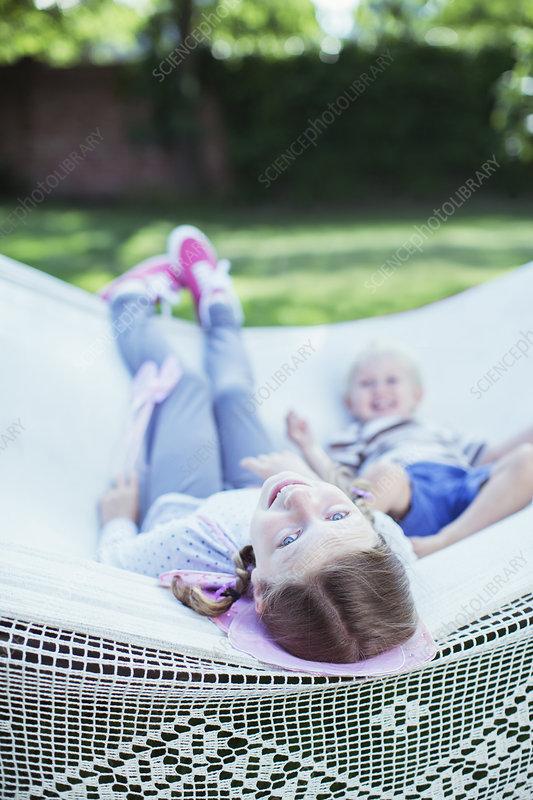 Children relaxing in hammock outdoors