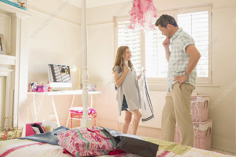 Father helping daughter pick clothing
