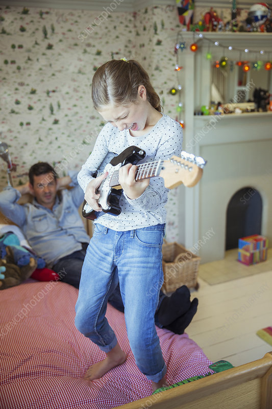 Girl playing guitar for father in bedroom