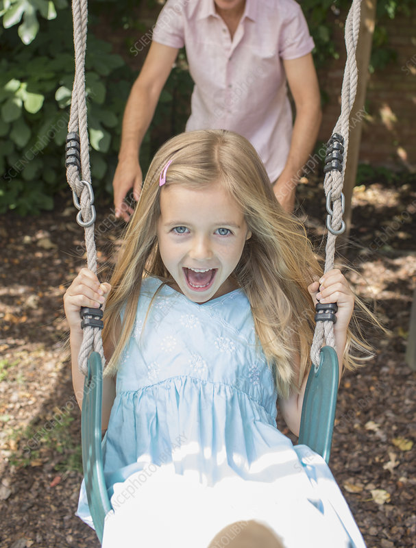 Father pushing daughter in swing