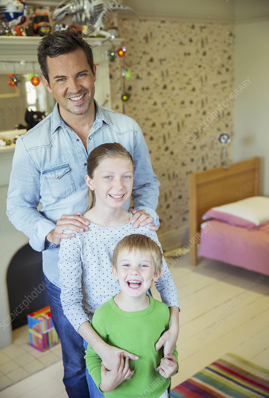 Father and children smiling in bedroom
