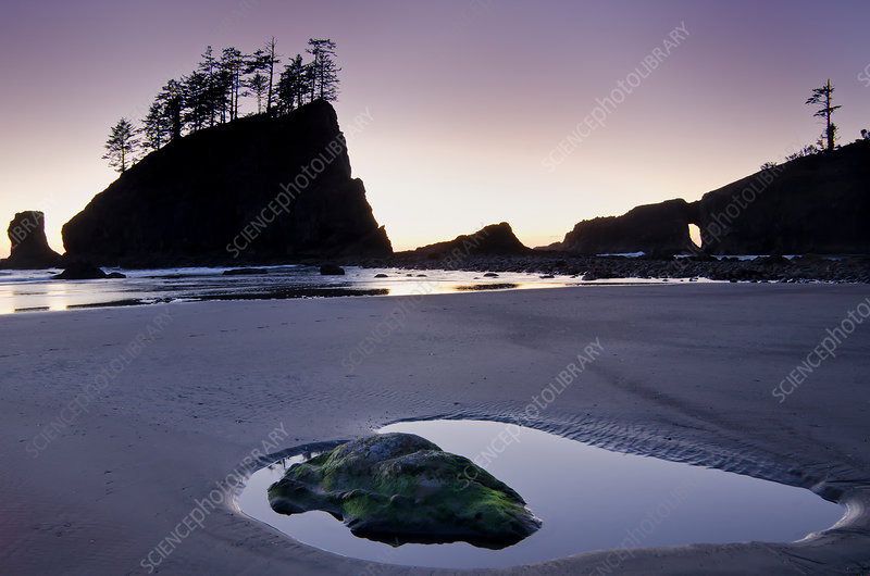 Silhouette of cliffs on beach at low tide