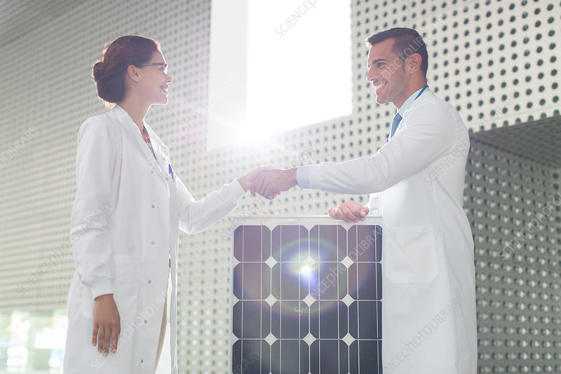 Scientists handshaking at solar panel