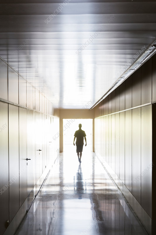 Silhouette of person walking in corridor