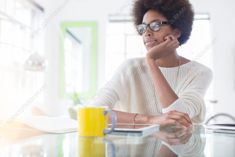 Pensive woman using tablet at table