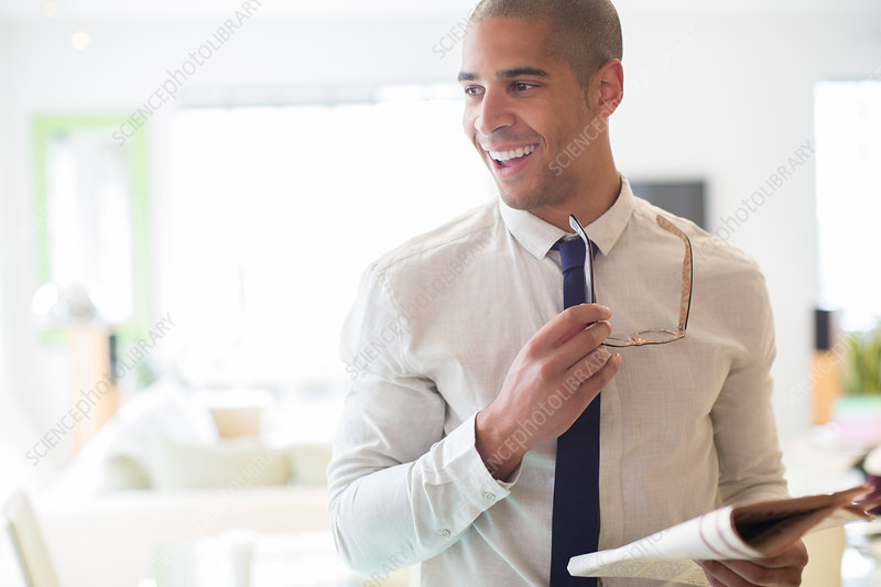 Businessman holding newspaper in kitchen