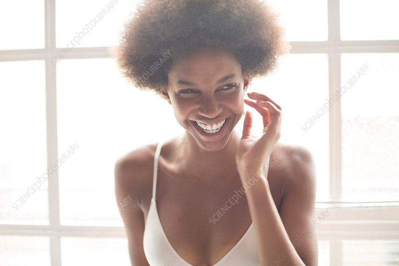 Smiling woman in bra standing by window