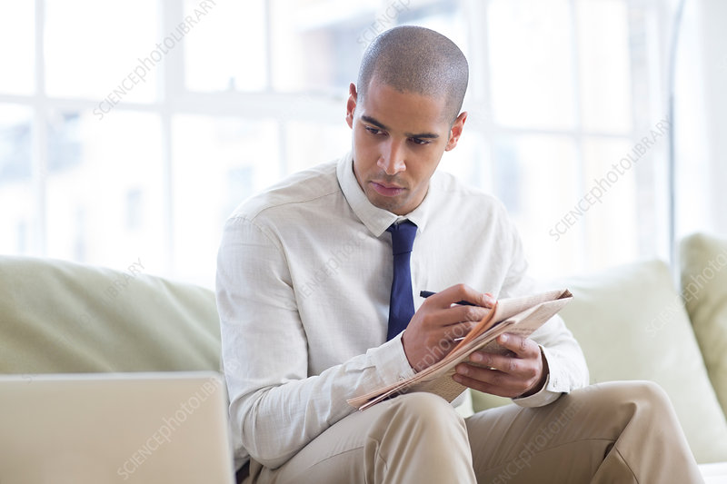 Businessman making notes from laptop