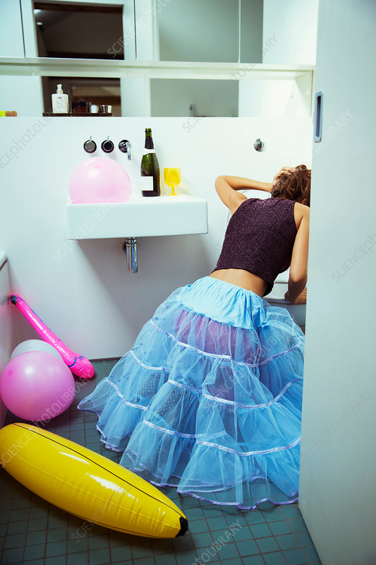 Woman vomiting into toilet at party