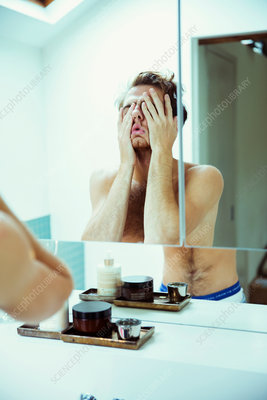 Hungover man covering face at mirror