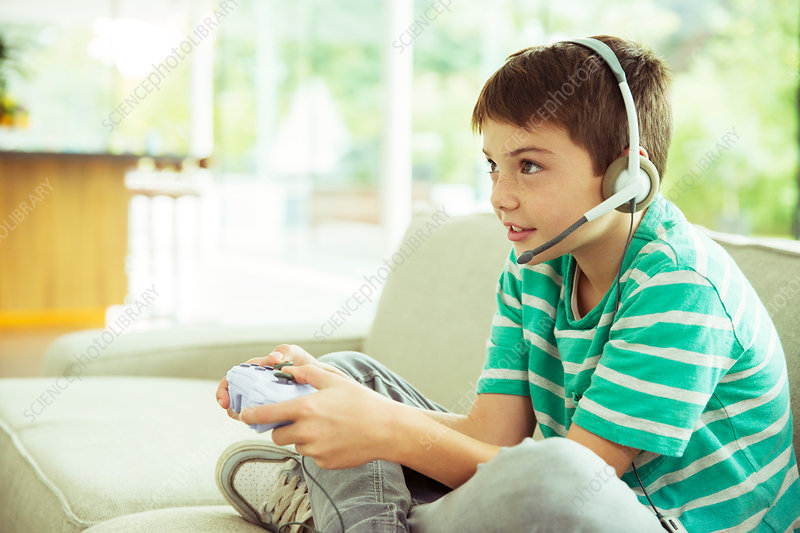 Boy playing video games on sofa