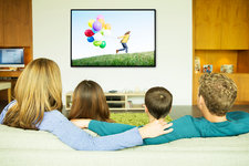 Family watching television in living room