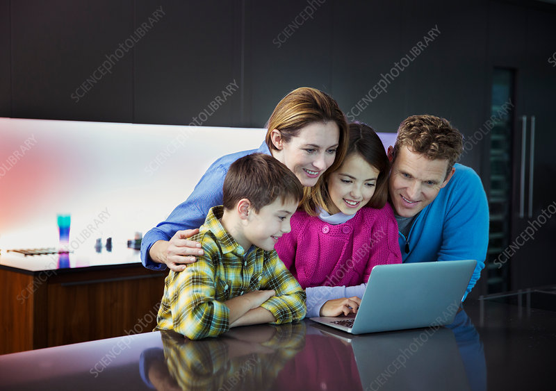 Family using laptop together in kitchen