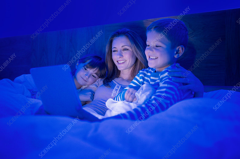 Mother and children using tablet in bed