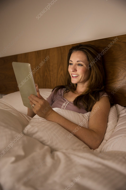 Woman using digital tablet in bed