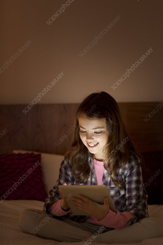 Girl using digital tablet on bed